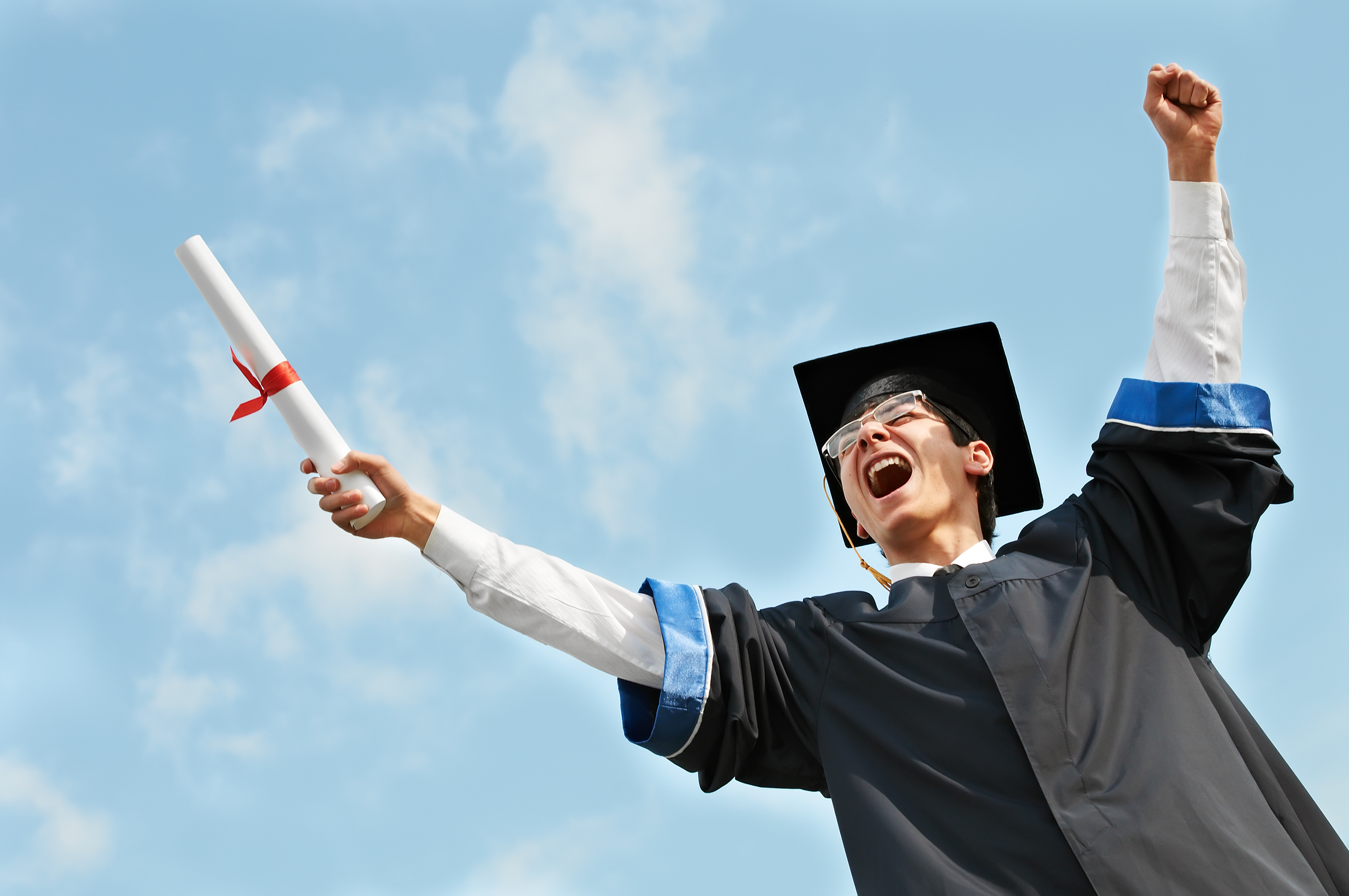 excited graduate student in gown with risen hands holding diploma over blue sky